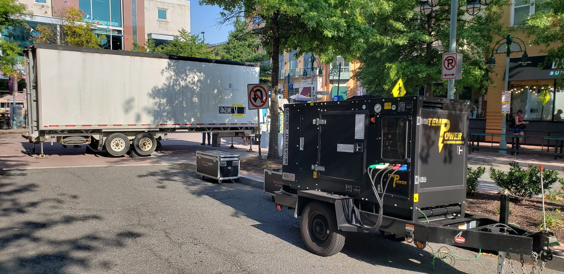 A portable quiet-run generator and mobile stage are set up for an event