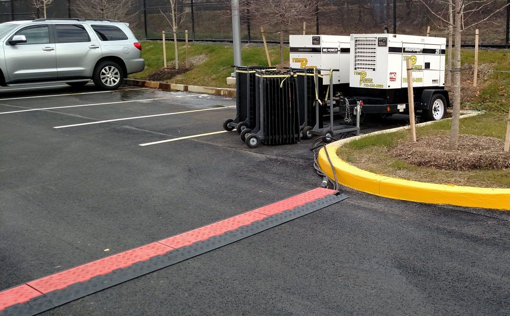 Generators provide power for a special event. Cords cross a roadway inside cable ramps protected from vehicle traffic